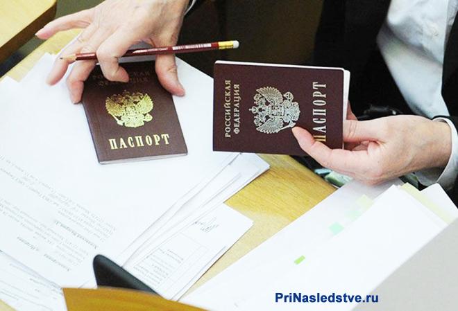 Девушка сидит за столом и смотрит данные в папортах