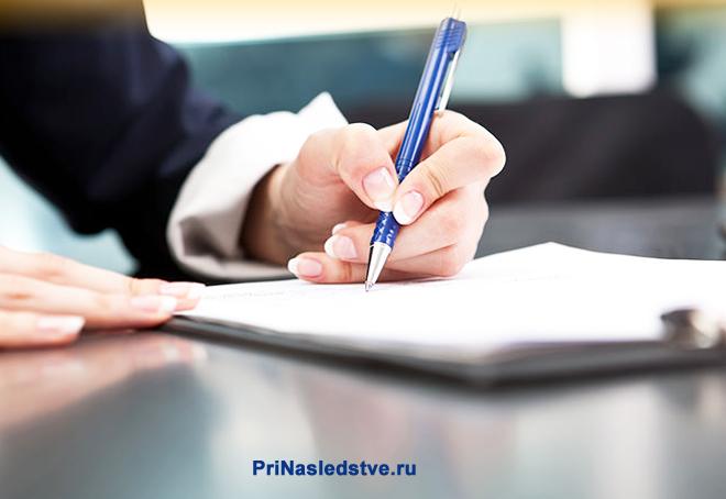 Человек пишет синей ручкой на листке