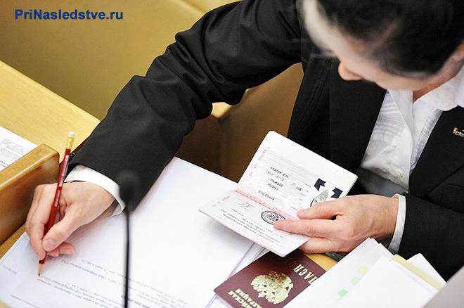 Женщина сморит в паспорт и переписывает данные в тетрадь