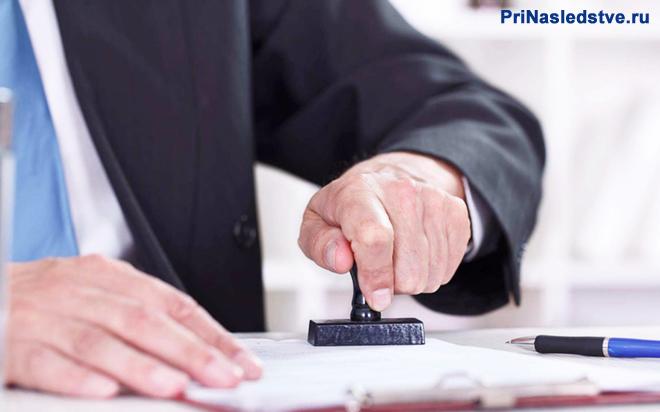 Мужчина в черном костюме и синем галстуке ставит печать на документах