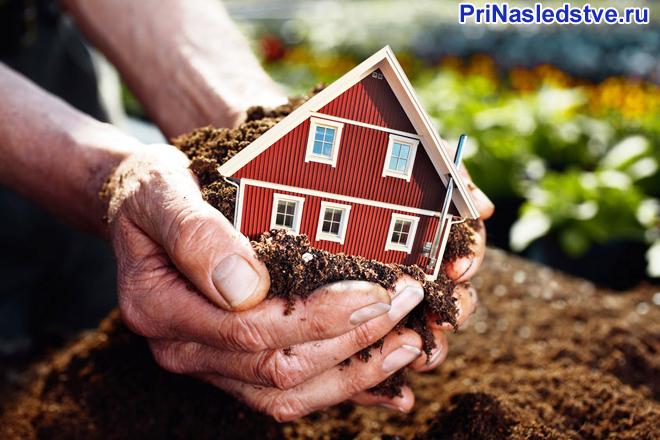 Человек берет в руки дом с землей