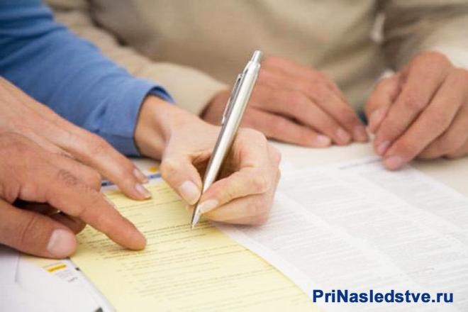 Мужчина пишет на желтых и белых листочках