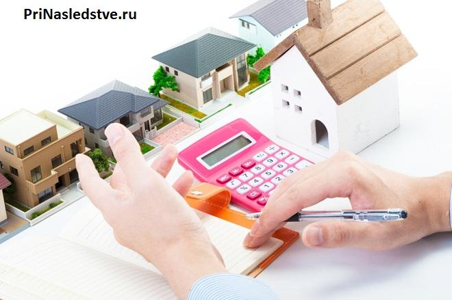 Женщина считает стоимость домов на калькуляторе