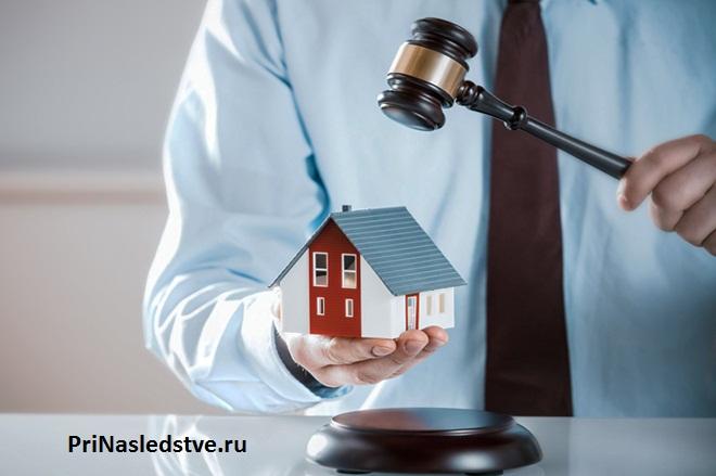 Мужчина в голубой рубашке держит в руке домик и молоточек