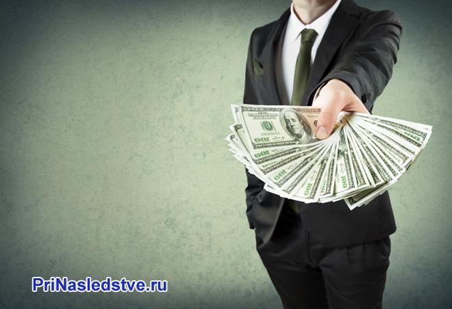Бизнесмен держит в руке веер из денежных купюр