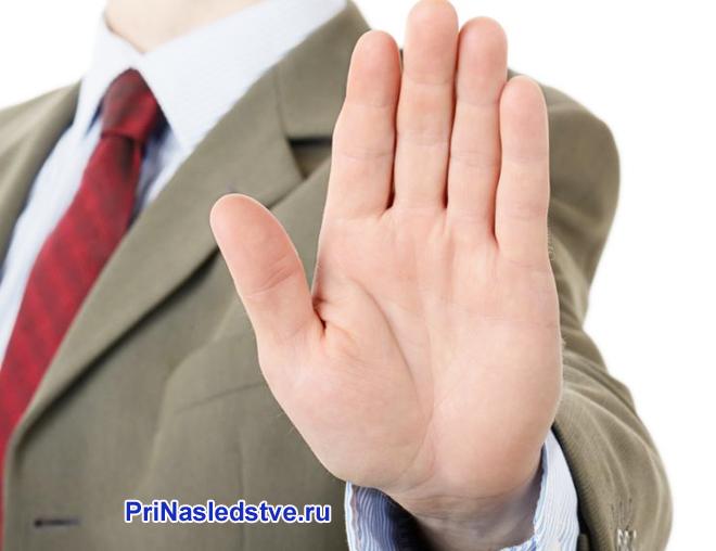 Бизнесмен показывает ладонью знак отказа