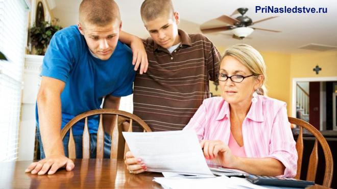 Женщина читает бумагу за столом, рядом стоят двое парней