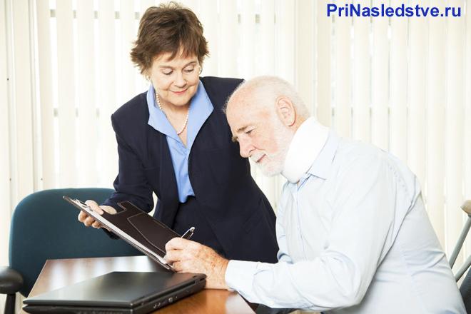 Мужчина в возрасте ставит свою печать на документе, который ему подает женщина