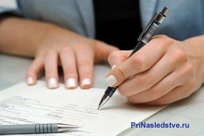 Девушка пишет ручкой на листе бумаги