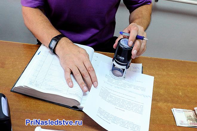 Мужчина ставит печать на документе, сидя за столом