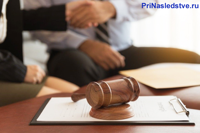 Бизнесмен жмут друг другу руки, на переднем фоне лежит судебный молоточек