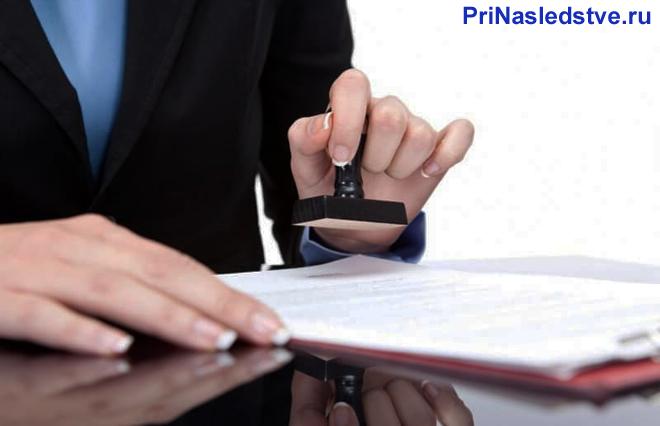 Женщина в деловом костюме ставит печать на документе