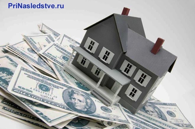 Серый домик стоит на денежных купюрах