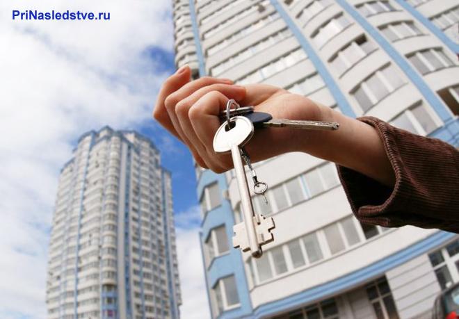 Девушка держит ключи от квартиры в руке на фоне многоэтажного дома