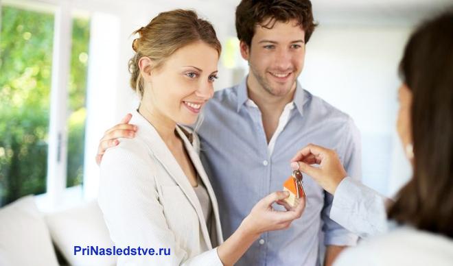 Женщина отдает ключи молодой паре