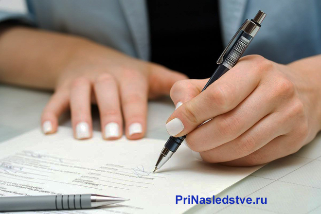 Женщина подписывает ручкой документы