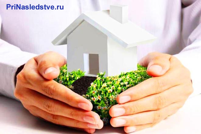 Мужчина держит в руках белый дом на травке