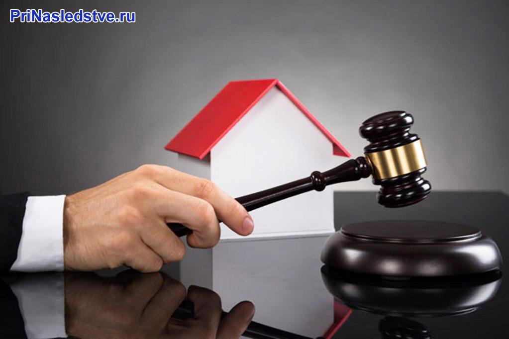 Бизнесмен держит молоточек на фоне дома с красной крышей