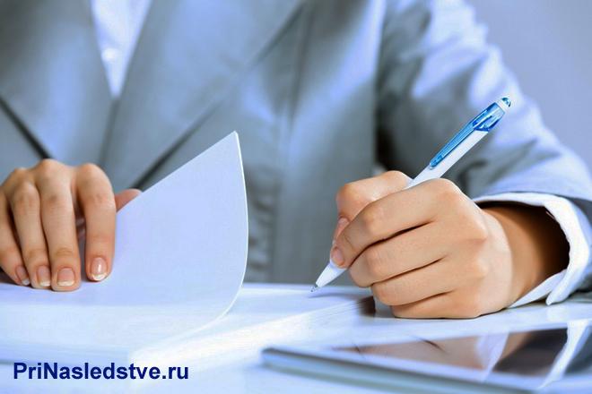 Мужчина в деловом костюме заполняет лист бумаги