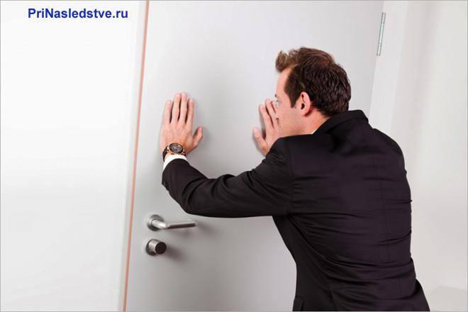 Бизнесмен придерживает дверь