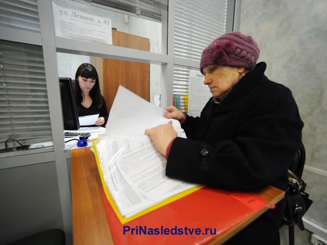 Женщина сдает документы в окно приема