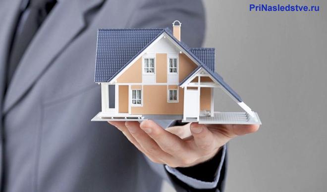Бизнесмен держит в руке частный дом
