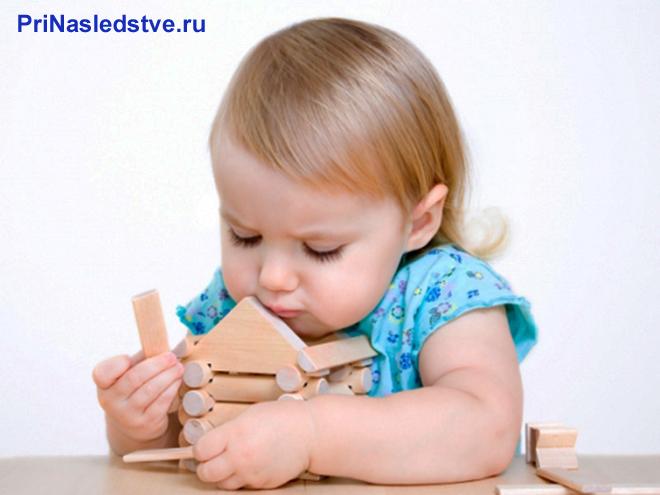 Девочка собирает деревянный домик