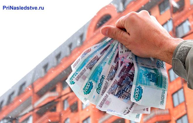 Человек держит в руках денежные купюры, на заднем фоне многоквартирный дом