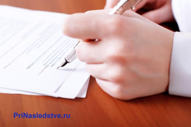 Мужчина пишет на листке бумаги за столом