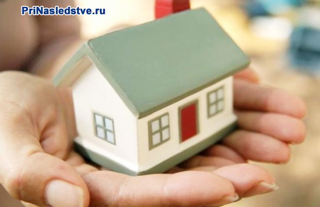 Девушка держит на ладони домик с салатовой крышей