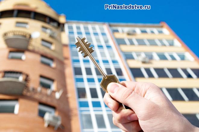 Мужчина держит в руке ключ от квартиры