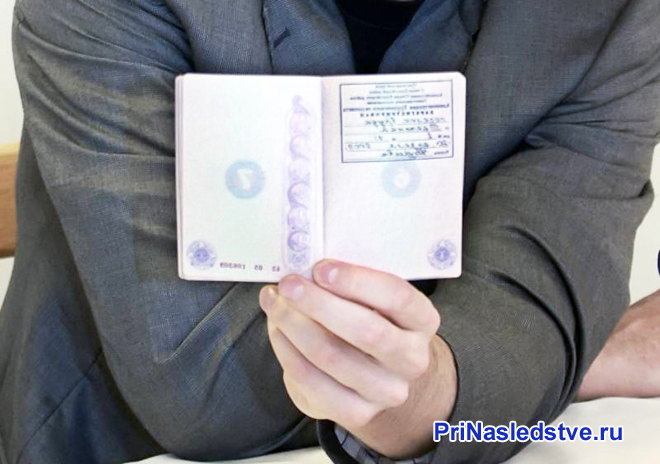 Бизнесмен держит в руке свой паспорт