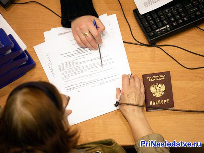 Женщина заполняет документы за столом