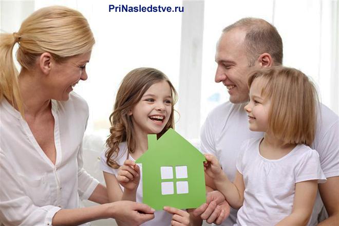 Счастливая семья в белой одежде, девочка держит салатовый домик