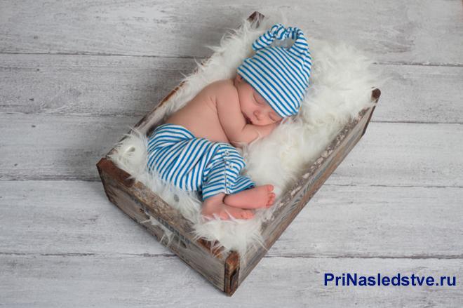 Малыш в полосатом костюме спит