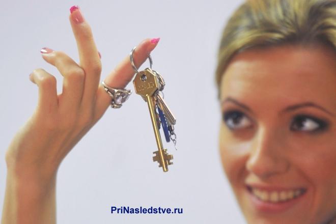 Блондинка держит в руке связку ключей