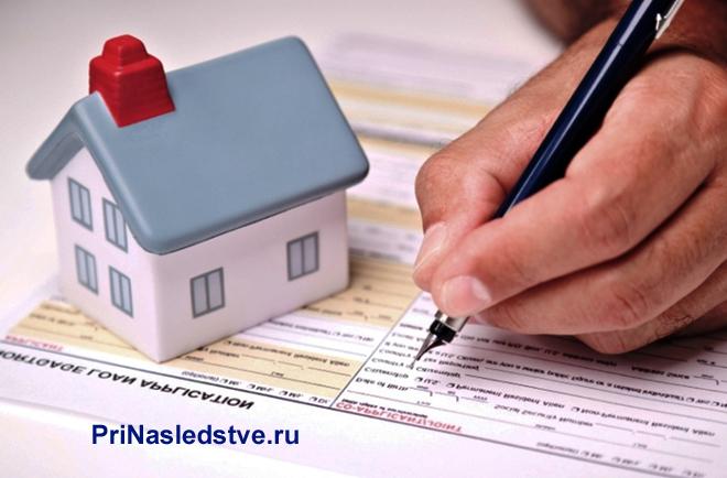 Человек заполняет ручкой бланк, рядом стоит домик с голубой крышей