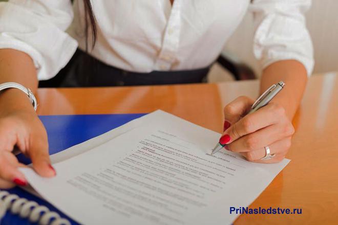 Девушка в белой рубашке сидит за столом и заполняет бумаги