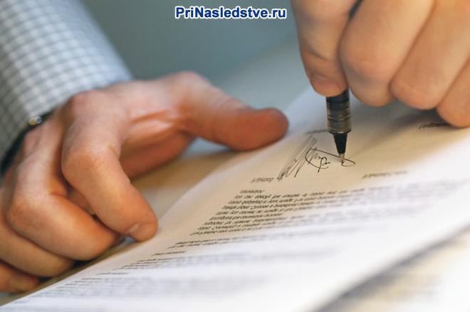 Мужчина в клетчатой рубашке ставит свою подпись на документе