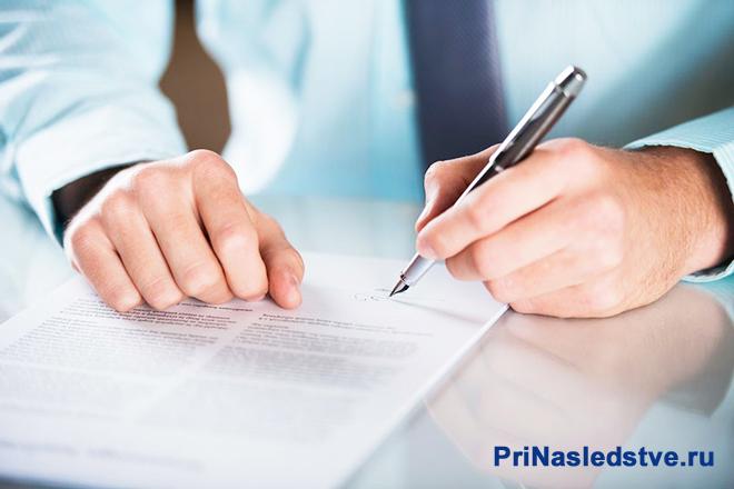 Бизнесмен сидит на столом и ставит свою подпись на договоре