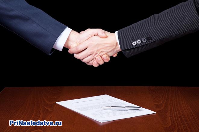 Рукопожатие бизнес-партнеров, на столе лежит договор