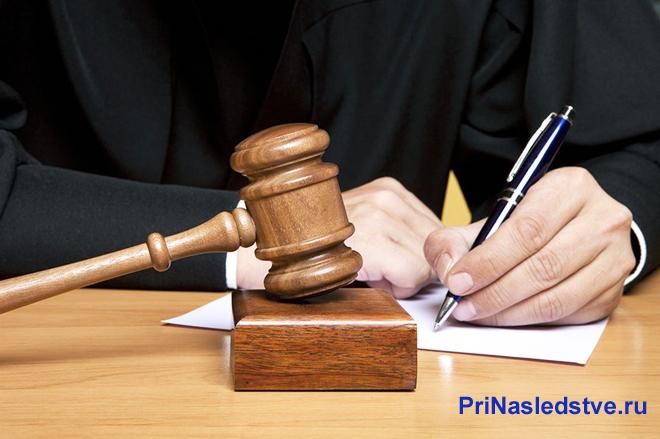 Судья пишет на листе бумаги, рядом на столе лежит молоточек