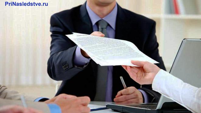 Бизнесмен передает бизнес-партнеру в руки документ