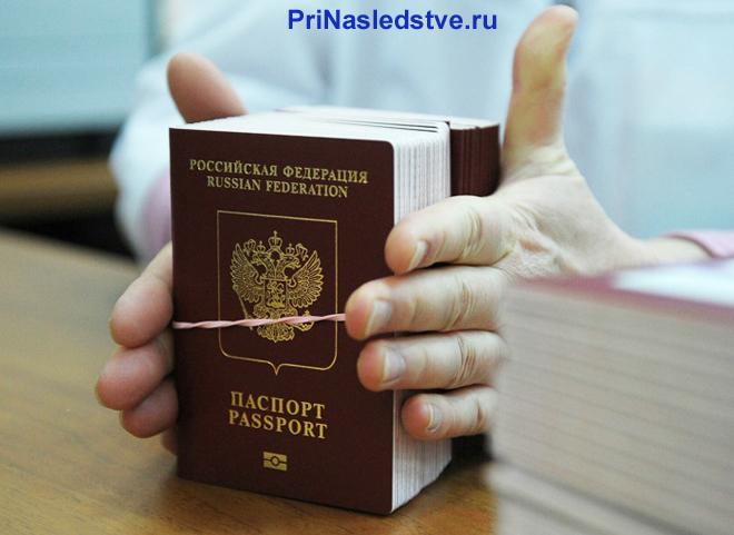 Человек держит стопку паспортов