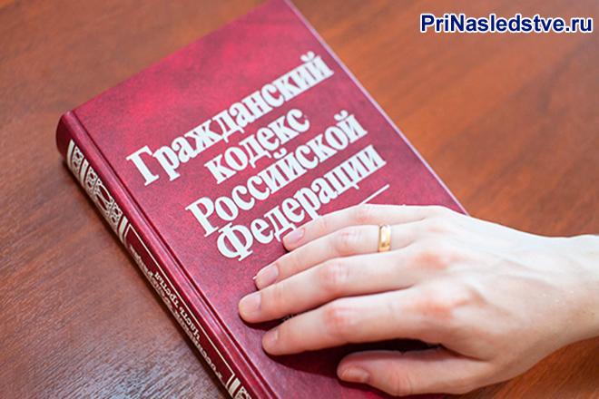 Рука человека лежит на ркасной книге Гражданский кодекс РФ