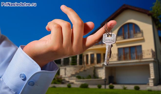 Мужчина держит в руке ключ от особняка