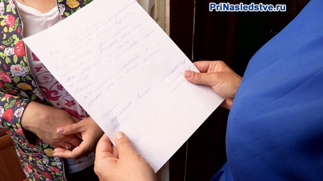 Женщина читает запись на листке бумаги