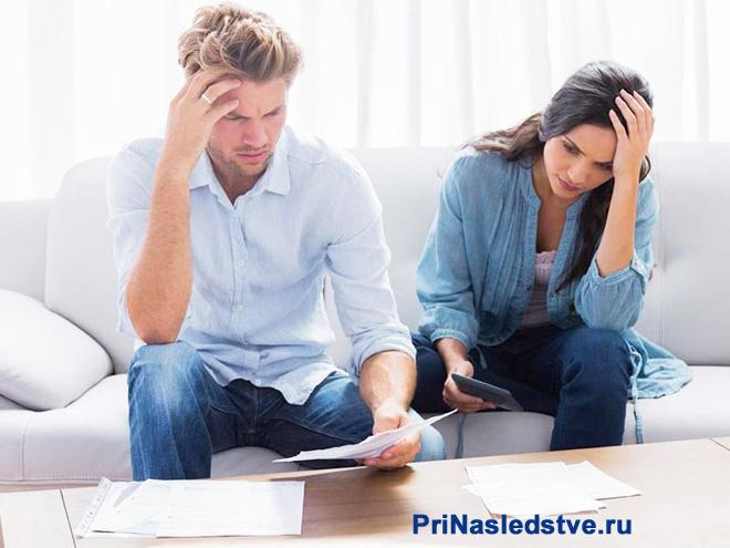 Мужчина и женщина в раздумьях сидят на диване и читают документы