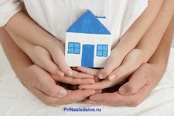 Семья держит вместе в руках бумажный домик