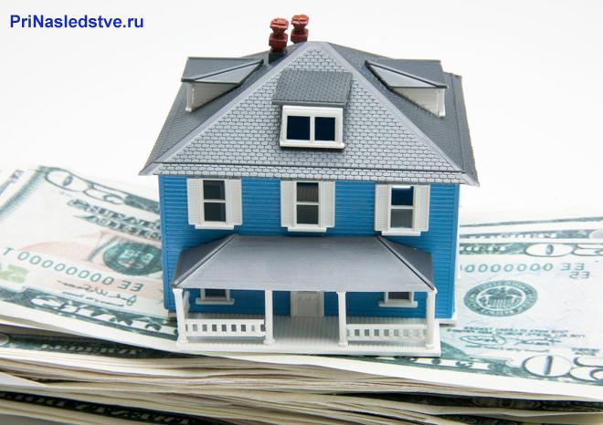 Синий домик стоит на пачке денег
